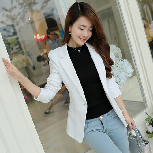 vit kavaj med svart tröja med rund halsringning och ljusblå jeans