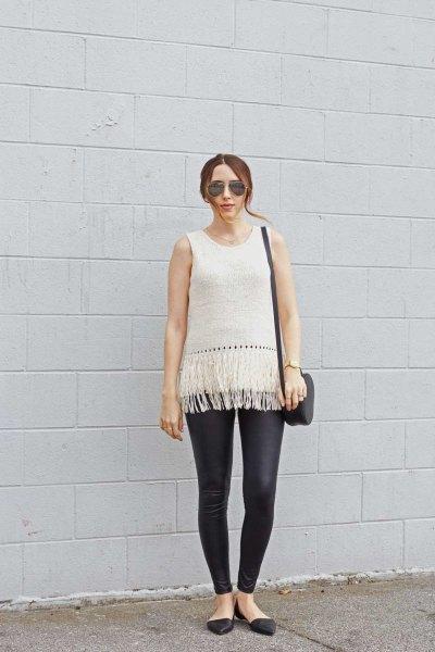 vit ärmlös stickad tröja svart läder gamacher
