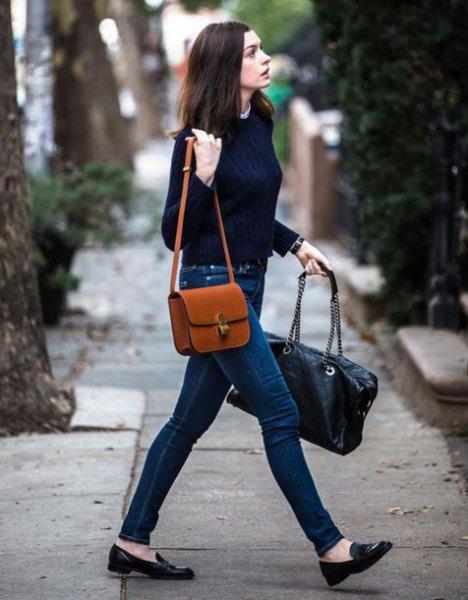brun läder axelväska med svart tröja och mörkblå jeans