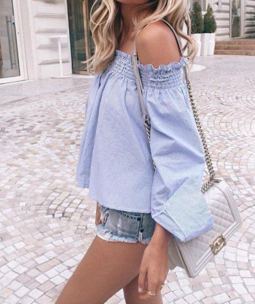 off-the-shoulder ljusblå blus med mini-jeansshorts och ljusrosa handväska
