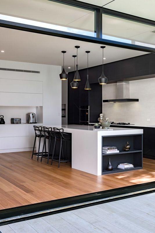 Trägolv svart hängande lampor Vit köksskåp svart.