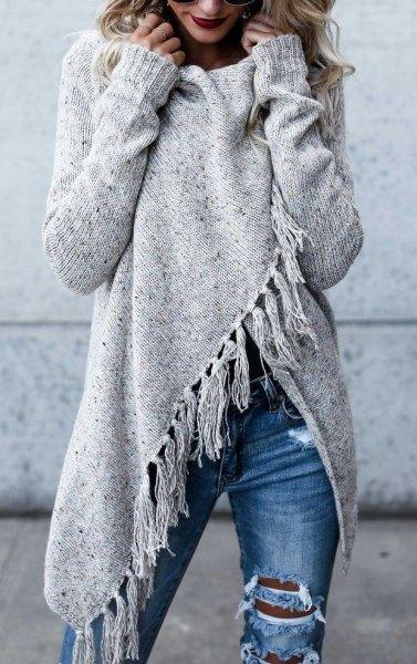 grå omslagströja med fransar och blå, förstörda jeans