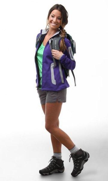 blå vandringsjacka med grå mini-shorts och svarta trailskor