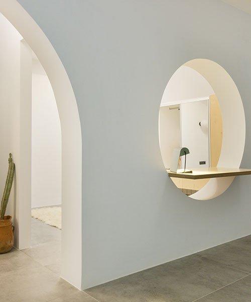 skulpturell skiljevägg med böjda öppningar organiserar lägenhet.