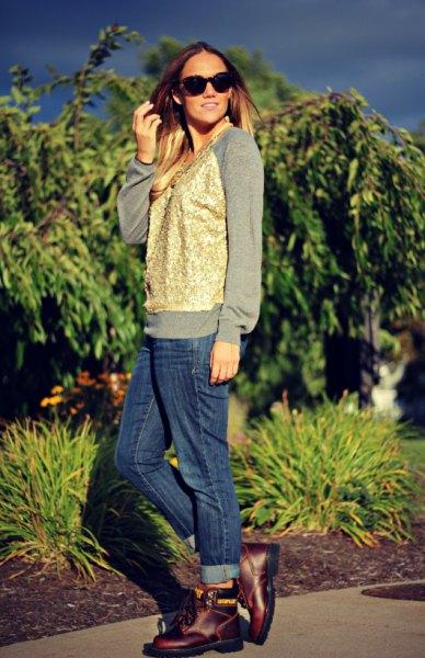 grå tröja med guldväst och blå jeans med manschett