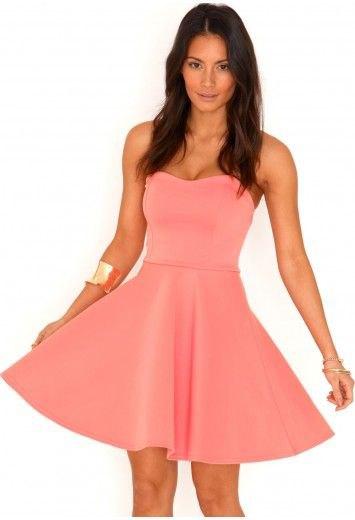 Axelbandslös miniklänning i rosa och flare med ett guldarmband