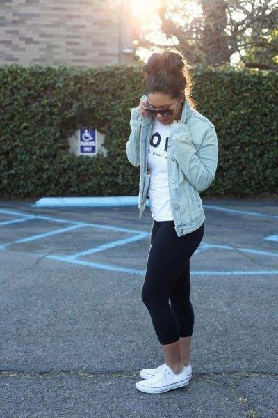 blå jeansjacka med vit T-shirt och svarta, smala löpbyxor