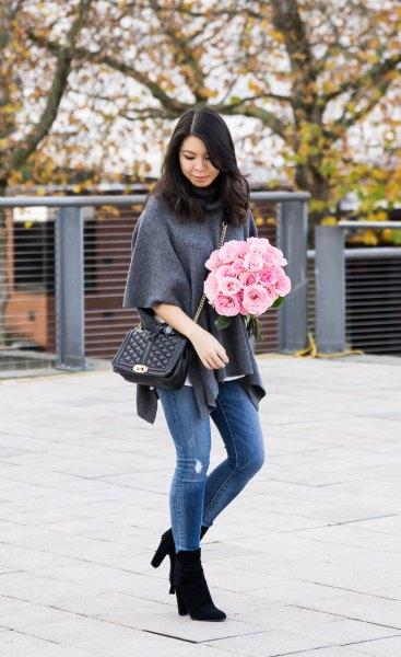 grå ponchotröja med halva ärmar, blå jeans och svarta stövlar