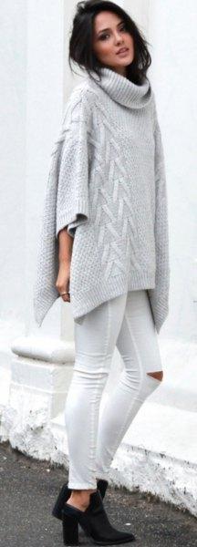 grå tröja med ponchotröja med kablar och vita skinny jeans