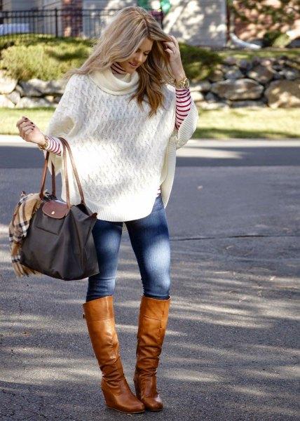 vit kabelstickad ponchotröja med blå skinny jeans och knähöga stövlar i brunt läder