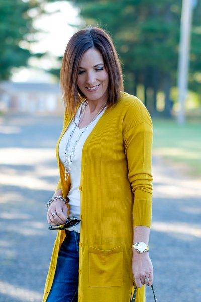 Stickad tröja med en vit linne med en urringning och blå jeans