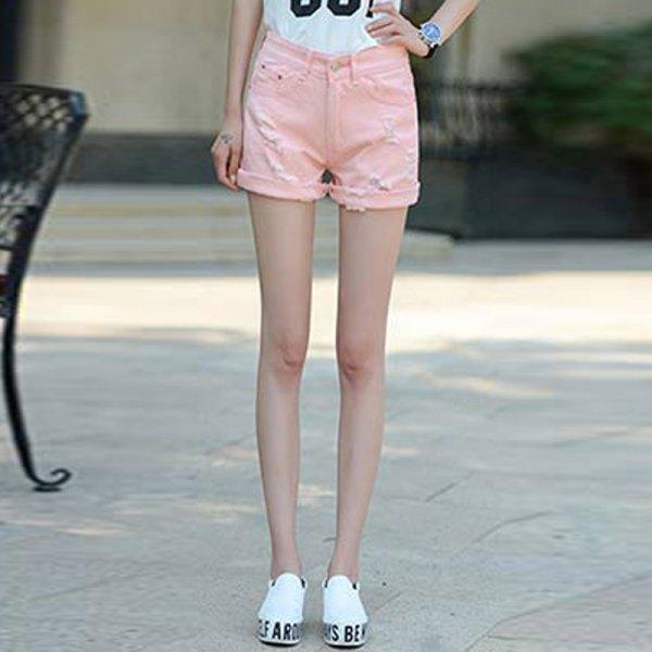 vit tryckt t-shirt med ljusrosa shorts och sneakers med muddar