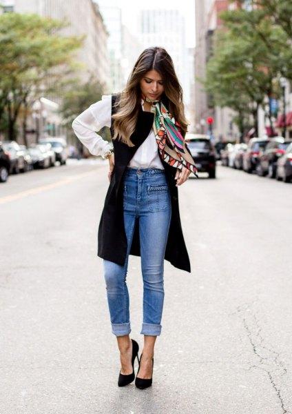vit skjorta med knappar, svart långväst och blå jeans med hög midja