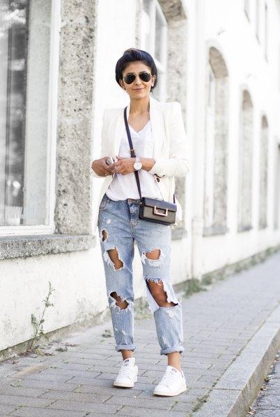vit kavaj med V-ringad t-shirt och kraftigt rippade jeans