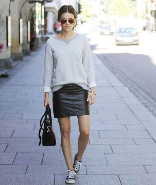 grå tröja med minikjol och svarta lädertränare