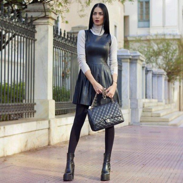 svart läder tank passform och flare mini läder veckad kjol och stövlar
