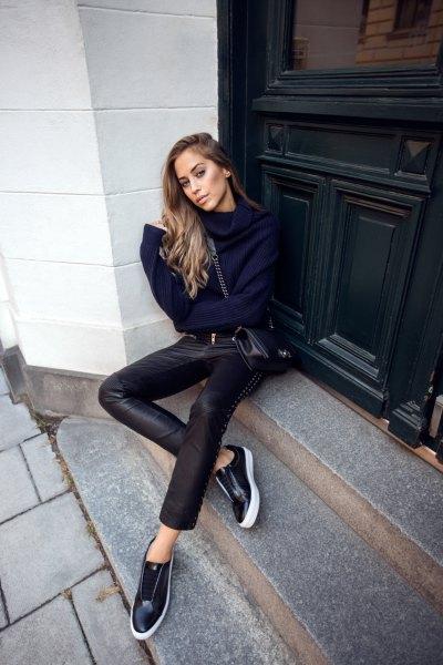 Mörkblå stickad tröja med halsringning och låga sneakers i svart läder