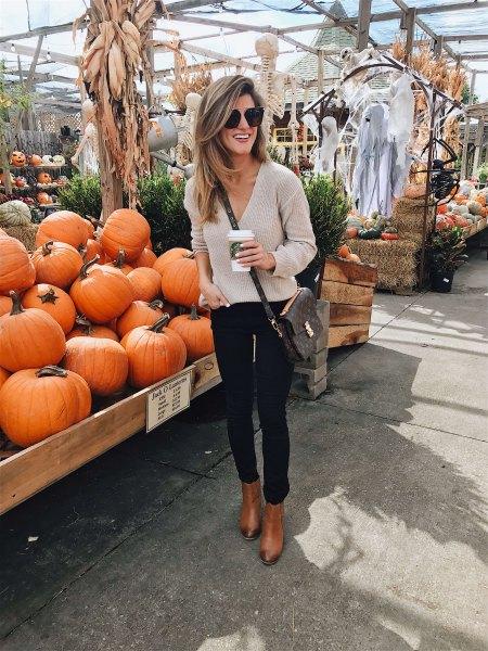 Ljusrosa V-ringad tröja och svarta skinny jeans