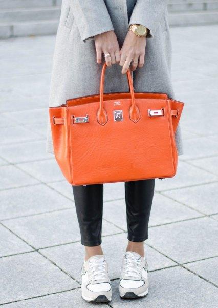 grå ullrock med svarta leggings och orange läderhandväska