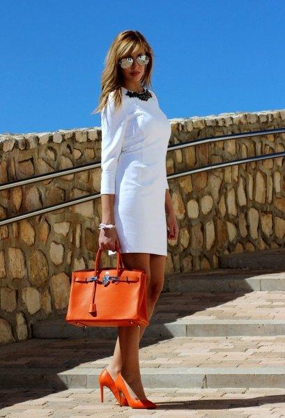 vit mini-klänning med tre fjärdedelar och orange läderhandväska