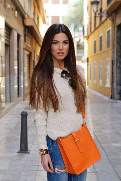 vit tröja med rund halsringning, blå pojkvänjeans och en orange handväska