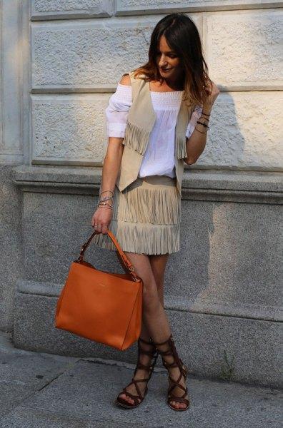 Vit off-the-shoulder blus med en crepe fransad väst och en orange handväska