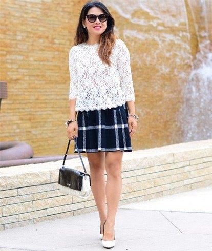vit spetsblus med kantad fåll och svart rutig kjol