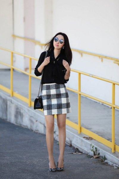 Blus med knappstängning och svart rutig minikjol