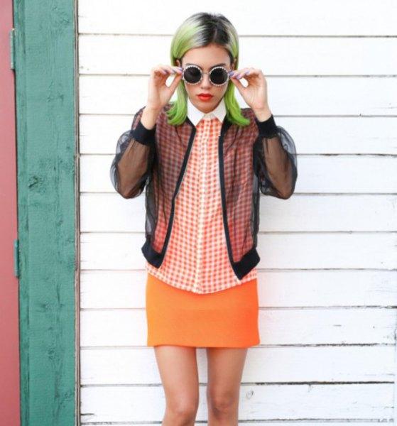 svart jacka med rutig skjorta och orange kjol