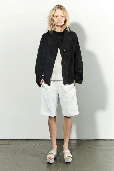 svart bomberjacka med ljusrosa tröja och vita långa shorts