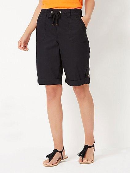 Senapsgult linne med svarta, knälånga shorts med en avslappnad passform