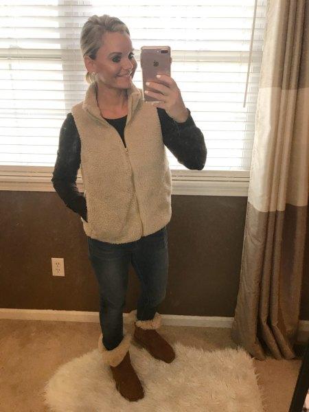rodnande rosa väst med dragkedja, blå skinny jeans och pälsstövlar