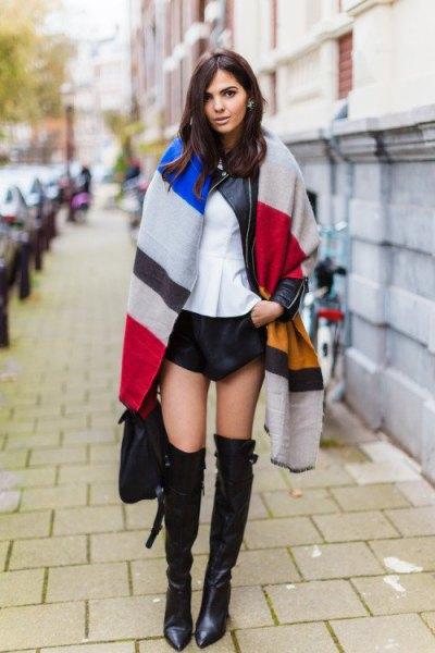 mångfärgad överdimensionerad halsduk med svarta minishorts och långa stövlar