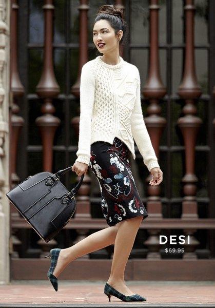 vit kabelstickad tröja och svart knälång blommig kjol