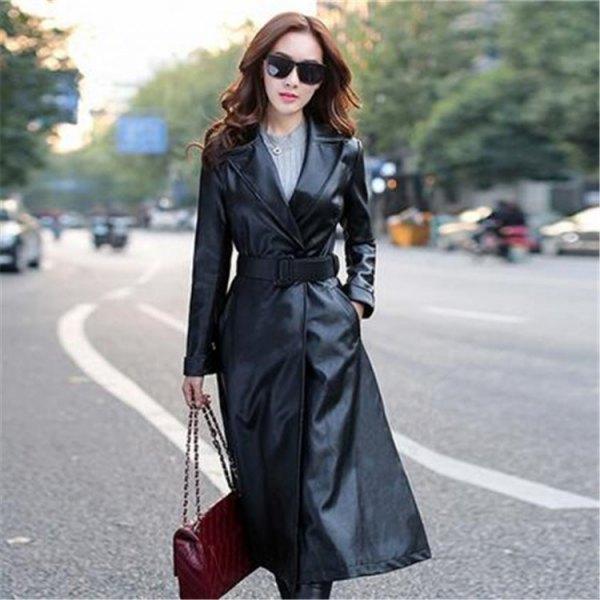 svart trenchcoat i svart läder med bälte, grå stickad tröja