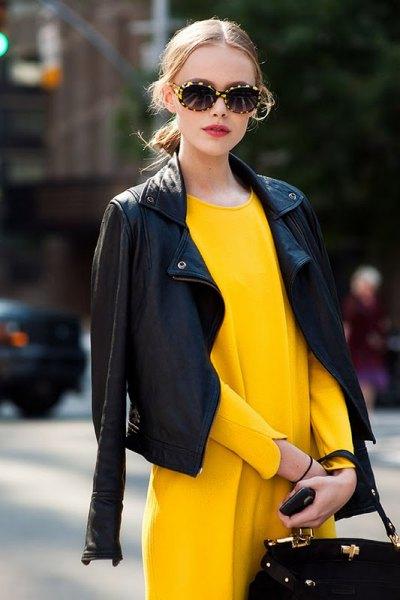 draperad svart skinnjacka över axlar gul klänning