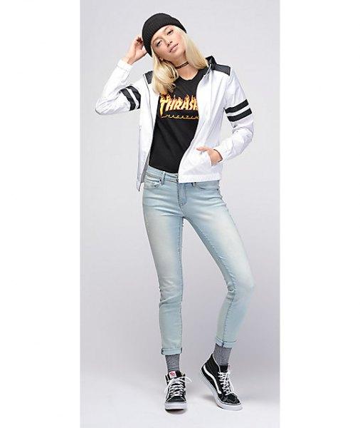 vit vindjacka med svart grafisk t-shirt och ljusblå skinny jeans