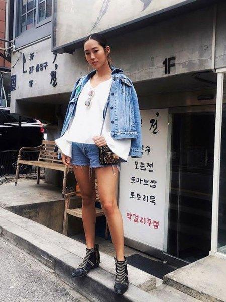 blå jeansjacka med vit blus med klockärmar och mini-shorts