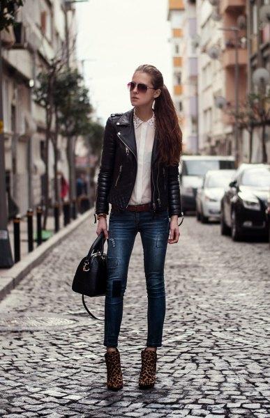 svart skinnjacka med vit skjorta och smala jeans