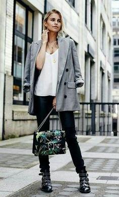 grå kavaj med vit chiffongblus med V-ringning och läderstövlar med spikar