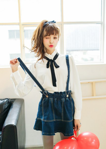 vit skjorta med knappar, svart fluga och mörkblå veckad kjol