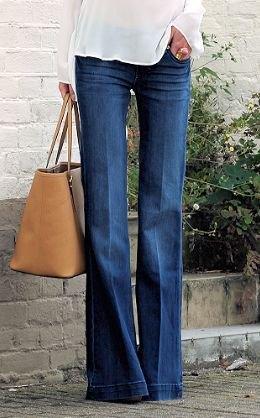 vit chiffongblus med utsvängda jeans och handväska i brunt läder
