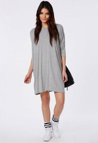 grå t-shirt klänning med svart läder axelväska och vita löparskor