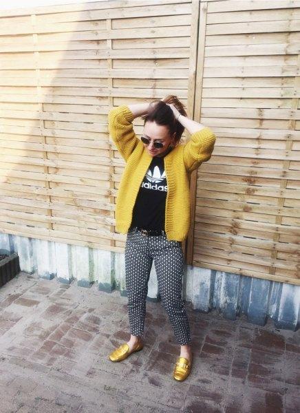 gul kofta med svart tryckt T-shirt och prickade byxor
