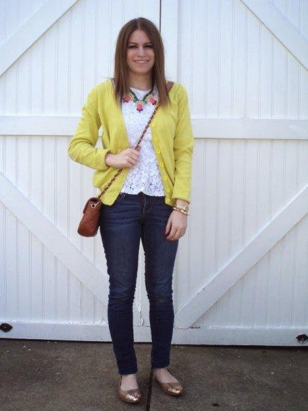 gul kofta med vit spets topp och smala jeans