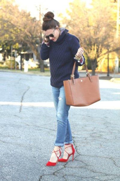 svart stickad tröja med blå jeans med muddar och röda klackar