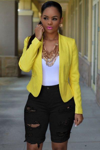 gul blazer med långa, midjiga shorts i svart denim