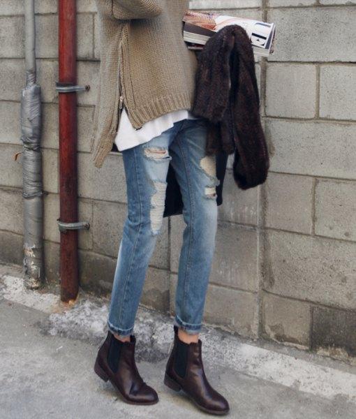 grå tröja med slits i jeans och svarta läderstövlar med dragkedjor