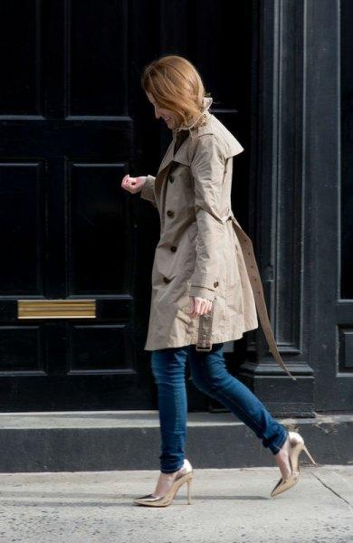 grå longline parkajacka med mörka smala jeans och guldklackar