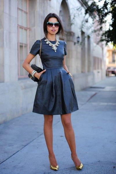 Mini-klänning i svart och fläckat läder med klackar i spetsig tå i metalliskt guld